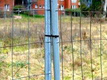 Poorten in de metaalomheining die door de plastic strook wordt gesloten stock fotografie