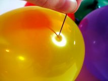 Pop!. Close up of needle pushing into surface of balloon royalty free stock images