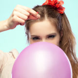 Pop it. Pretty girl is going to pop a balloon with a pin stock photo
