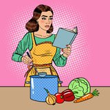 Pop Art Beautiful Housewife Cooking Soup in the Kitchen with Book of Recipes. Vector illustration Royalty Free Stock Image