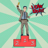 Pop Art Businessman Holding Golden Winners Cup. Pop Art Happy Businessman Holding Golden Winners Cup on First Place Podium. Vector illustration Royalty Free Stock Image