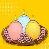 Pop art Easter candles in the shape of an egg. Three pieces of different colors with fire, in a basket nest and flowers. Color background. Comic book style Royalty Free Stock Images
