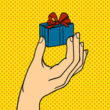 Pop art hand with gift box vector illustration. Stock Images