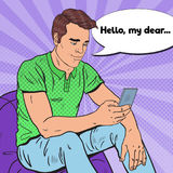 Pop Art Handsome Man is Reading Text Message on Smartphone. Mobile Technologies Royalty Free Stock Photography
