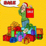 Pop Art Happy Woman in Santa Hat with Shopping Bag and Huge Gift Boxes on Christmas Sale Royalty Free Stock Photos
