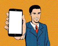 Pop art man with a phone. Pop art suited-up man with a smartphone with blank screen. Close-up view of a mobile phone. Halftone background Royalty Free Stock Photo