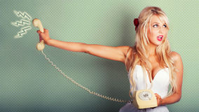 Comic Portrait Of A Blond Pin-up Girl With Phone. Pop Art Portrait Of A Beautiful Blonde Pin-up Girl On Hold With Call Waiting Music Playing In A Poor Customer Royalty Free Stock Image