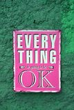 Pop art style vivid pink signboard of EVERYTHING is going to be OK on the rough Green wall. Texture Background royalty free stock image