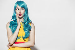 Pop art woman portrait wearing blue curly wig. And bright yellow dress. White background. Space for text Royalty Free Stock Photography