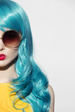 Pop art woman portrait wearing blue curly wig and sunglasses. stock photo