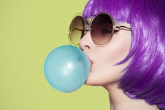 Pop art woman portrait wearing purple wig. Blow a blue bubble Royalty Free Stock Photography