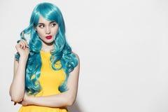Pop-Arten-Frauenporträt, das blaue gelockte Perücke trägt Lizenzfreies Stockbild