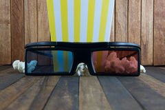 Pop corn and 3d glasses on wood background royalty free stock photography