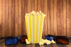 Pop corn and 3d glasses on wood background stock photography