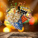 Pop-corn, movie tickets, clapperboard and other things in motion. Cinema concept Royalty Free Stock Photos