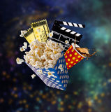 Pop-corn, movie tickets, clapperboard and other things in motion. Cinema concept Royalty Free Stock Images