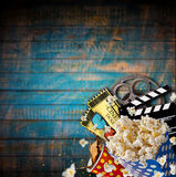 Pop-corn, movie tickets, clapperboard and other things in motion. Cinema concept Royalty Free Stock Photo