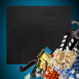 Pop-corn, movie tickets, clapperboard and other things in motion. Cinema concept Royalty Free Stock Image