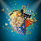 Pop-corn, movie tickets, clapperboard and other things in motion. Cinema concept Stock Photography