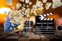 Pop-corn, movie tickets, clapperboard and other things in motion. Cinema concept Royalty Free Stock Photography