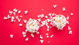 Pop corn in red paper cups on red color background stock images