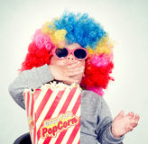 Pop corn time. Child with clown wig and sunglasses eating pop corn Royalty Free Stock Photography