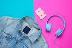 Pop culture attributes eighties. Denim jacket, headphones, audio cassette on a blue-pink background. Top view, 80s royalty free stock image