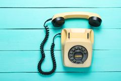 Pop culture attributes. Retro rotary telephone with a handset on a blue wooden table, top view royalty free stock image