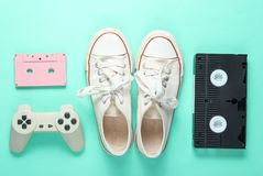 Pop culture attributes from 80s. On mint color background. Old sneakers, gamepad, audio cassette, videotape. Minimalism, top view stock images
