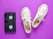 Pop culture attributes 80s. Retro white sneakers shoes, videotape on a purple background. Top view royalty free stock image