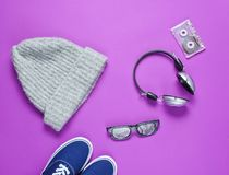 Pop culture attributes from the 80s. On a purple paper surface. Headphones, audio cassette, sneakers, hat, 3D glasses royalty free stock image