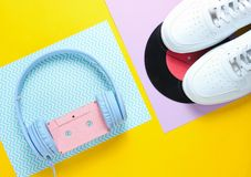 Pop Culture, retro 80s old fashioned objects. On a creative background. White sneakers, headphones with audio cassette, lp record. Top view. Flat lay royalty free stock photography
