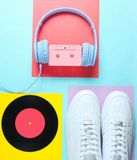 Pop Culture, retro 80s old fashioned objects. On a creative background. White sneakers, headphones with audio cassette, lp record. Top view. Flat lay stock image