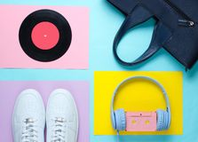 Pop Culture, retro 80s old fashioned objects. On a creative background. White sneakers, headphones with audio cassette, lp record, women's leather bag. Top stock photo