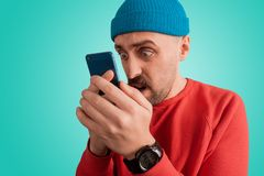 Pop-eyed guy staring at his smartphone with dismay emotion. Stunned man holding his mobile phone with both hands and and closely looking at something on the stock photos