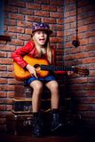 Pop music star. Modern child girl playing guitar and singing a song. Rock star, rock music, pop music concept Stock Photos