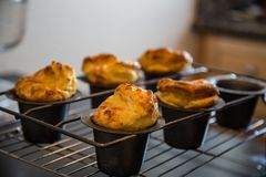 Pop Overs fresh out of the oven cooling in a rack Stock Photos
