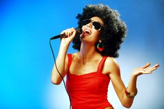 Pop singer. Attractive woman with afro hairstyle is singing expressively into the the microphone against blue background Stock Photo