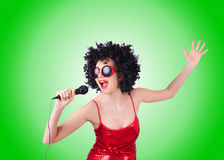 Pop star with mic in red dress against gradient Royalty Free Stock Images