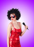 Pop star with mic in red dress against the Stock Images