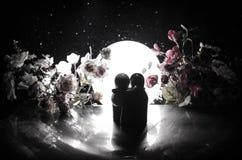 Pop twee die op lijst met bloemen en maandecoratie koesteren stak achtergrond met rook aan Het concept van de liefde Groet of gif Stock Afbeelding