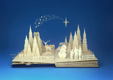 Pop-Up Book - Christmas Story. Styled 3D pop-up book with a theme including a family building a snowman, winter forest and stars Royalty Free Stock Images