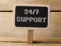 Poparcia 247 tekst pisze na Chalkboard przy drewnianym tłem Obrazy Stock