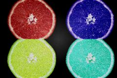 Popart juicy multi-colored orange on a dark background. Red, blue, green and yellow orange stock photo