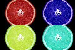 Popart juicy multi-colored orange on a dark background. Red, blue, green and yellow orange stock images