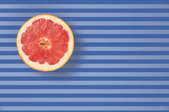 Popart style red grapefruit on a striped background top view Stock Images