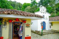 POPAYAN, COLOMBIA - FEBRUARY 06, 2018: Outdoor view of grocery store with handycrafts close to white small cathedral in Royalty Free Stock Images