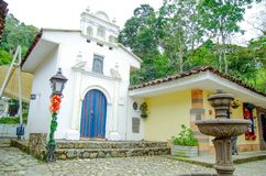 POPAYAN, COLOMBIA - FEBRUARY 06, 2018: Outdoor view of white small cathedral with a stoned fountain in Popayan town Stock Image