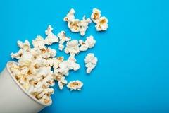 Popcorn από έναν κάδο εγγράφου ή ένα φλυτζάνι σε ένα μπλε υπόβαθρο στοκ φωτογραφία