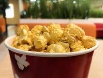 Popcorn καραμέλας στο κόκκινο κιβώτιο στο υπόβαθρο θαμπάδων στοκ φωτογραφία